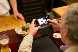 料理の写真を撮る外国人の写真素材 [FYI03054527]