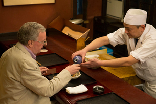 外国人に日本酒を注ぐ板前の写真素材 [FYI03054541]
