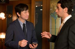 会話するスーツ姿の外国人と男性の写真素材 [FYI03054586]