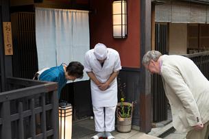 お辞儀をする外国人と板前と女将の写真素材 [FYI03054607]