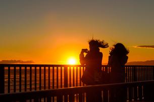 沈む夕日とそれを撮影している女性の写真素材 [FYI03056931]
