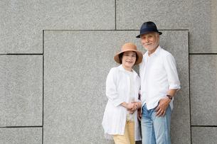 壁の前に立つシニア夫婦の写真素材 [FYI03057357]