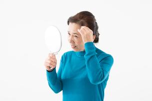 髪の毛が気になるシニアの女性の写真素材 [FYI03057374]