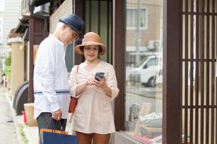 店頭ディスプレイを眺めるシニア夫婦の写真素材 [FYI03057399]
