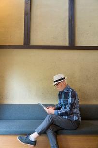 タブレットPCを操作するシニア男性の写真素材 [FYI03057402]