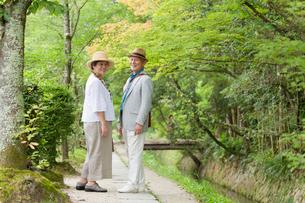 川沿いの遊歩道を歩くシニア夫婦の写真素材 [FYI03057410]
