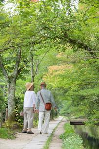 川沿いの遊歩道を歩くシニア夫婦の写真素材 [FYI03057416]