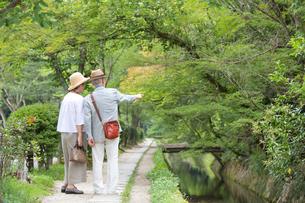 川沿いの遊歩道を歩くシニア夫婦の写真素材 [FYI03057417]