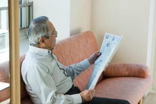 新聞を読むシニアの男性の写真素材 [FYI03057427]