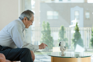 コミュニケーションロボットで遊ぶシニアの男性の写真素材 [FYI03057433]
