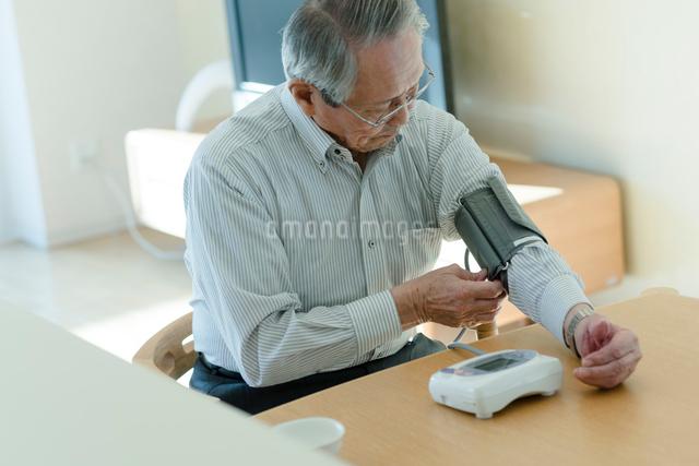 血圧を測るシニアの男性の写真素材 [FYI03057435]