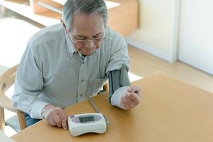 血圧を測るシニアの男性の写真素材 [FYI03057439]