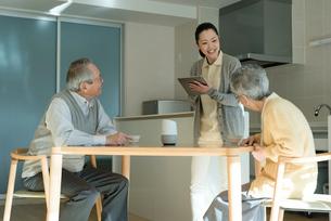 ホームヘルパーの問診を受ける老夫婦の写真素材 [FYI03057445]