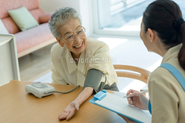 血圧を測るシニアの女性の写真素材 [FYI03057448]