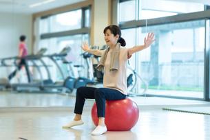 バランスボールで運動するシニアの女性の写真素材 [FYI03057449]