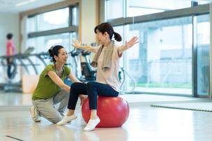 バランスボールで運動するシニアの女性の写真素材 [FYI03057452]