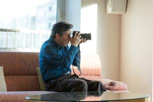 カメラをいじるシニアの男性の写真素材 [FYI03057485]