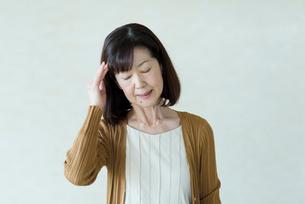 頭痛に悩まされるシニアの女性の写真素材 [FYI03057492]