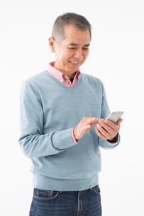 スマートフォンを操作するシニアの男性の写真素材 [FYI03057523]