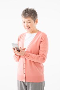 スマートフォンを操作するシニアの女性の写真素材 [FYI03057530]
