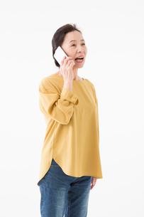 スマートフォンで話すシニアの女性の写真素材 [FYI03057550]