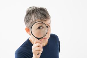 ルーペを覗き込むシニアの女性の写真素材 [FYI03057566]