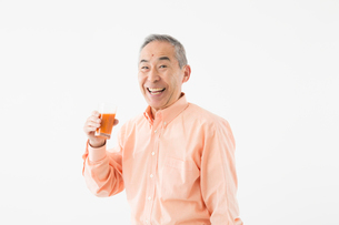 ジュースを持つシニアの男性の写真素材 [FYI03057592]