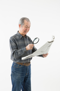 ルーペで新聞を読むシニアの男性の写真素材 [FYI03057610]