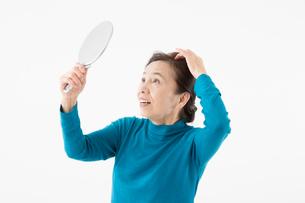 髪の毛が気になるシニアの女性の写真素材 [FYI03057613]