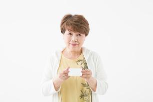 身分証明書を提示するシニアの女性の写真素材 [FYI03057625]