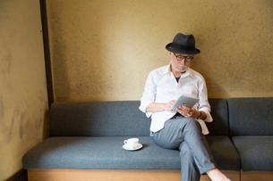 コーヒーを飲みながらタブレットPCを見るシニア男性の写真素材 [FYI03057710]