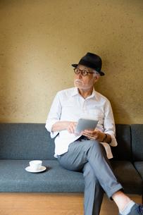コーヒーを飲みながらタブレットPCを見るシニア男性の写真素材 [FYI03057714]