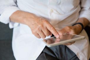 タブレットPCを操作するシニア男性の手元の写真素材 [FYI03057716]
