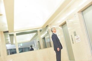 エレベーターを待つシニアのビジネスマンの写真素材 [FYI03057841]