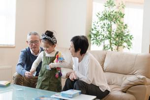 おじいちゃんとおばあちゃんと遊ぶ女の子の写真素材 [FYI03057862]