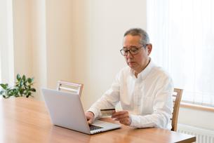 ノートパソコンを使うシニアの男性の写真素材 [FYI03057886]