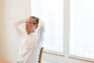 頭を抱えるシニアの男性の写真素材 [FYI03057888]