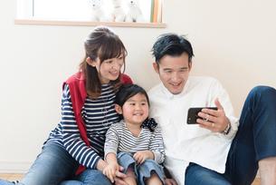 子供にスマートフォンを見せる父親の写真素材 [FYI03057921]