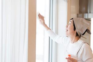 窓掃除をする年配の女性の写真素材 [FYI03057930]