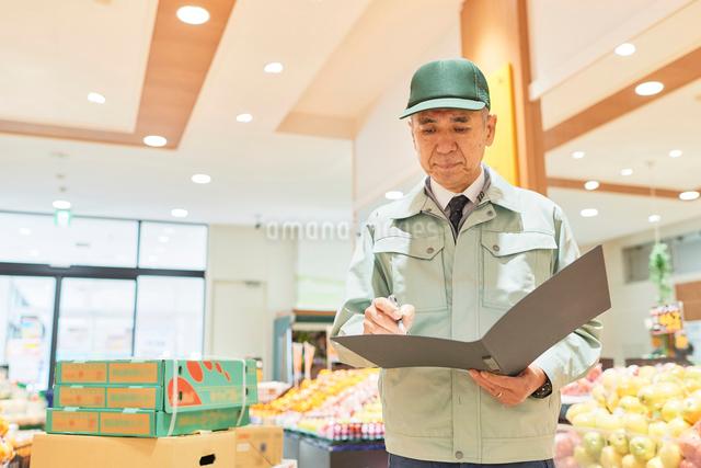スーパーでマネージャーとして働くシニア男性 在庫管理の写真素材 [FYI03057957]