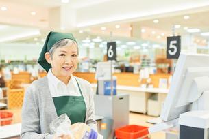 スーパーのレジで働くシニア女性の写真素材 [FYI03057966]