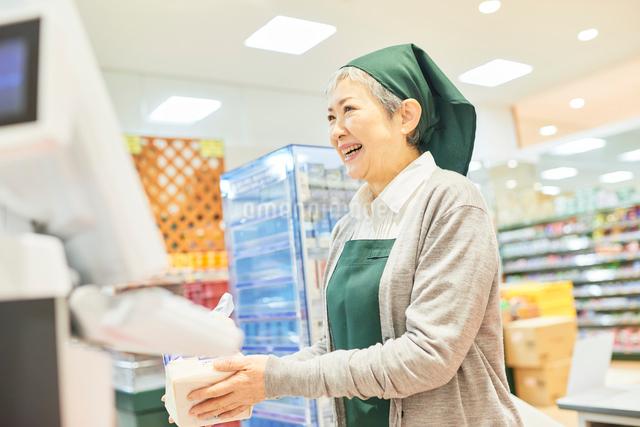 スーパーのレジで働くシニア女性の写真素材 [FYI03057967]