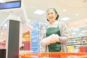 スーパーのレジで働くシニア女性の写真素材 [FYI03057971]
