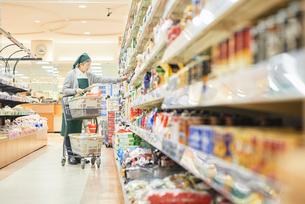 スーパーで買物代行をするシニア女性の写真素材 [FYI03057983]
