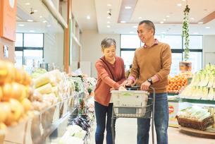 スーパーで買い物をするシニア夫婦の写真素材 [FYI03058006]