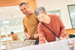 スーパーで買い物をするシニア夫婦の写真素材 [FYI03058007]