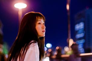 夜景をバックにした女性の写真素材 [FYI03058117]