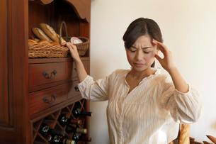 仕事中に頭痛をおこす女性の写真素材 [FYI03059429]