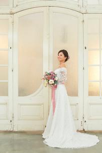 アンティークな扉の前に立つ美しい花嫁の写真素材 [FYI03059464]
