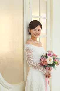 アンティークな扉の前に立つ美しい花嫁の写真素材 [FYI03059476]